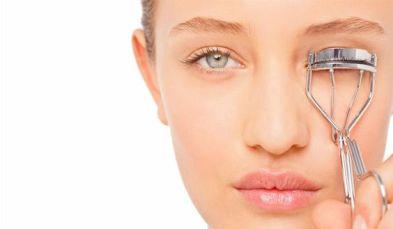 eyelash curler - woman using